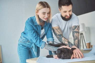 tattooed couple playing with french bulldog on blueprint at new home