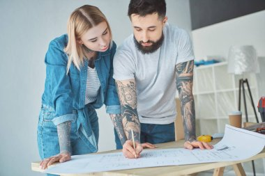 portrait of tattooed couple looking at blueprints on wooden tabletop at new home