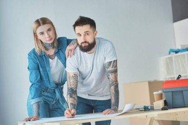 portrait of tattooed couple looking at camera while standing at blueprints on wooden tabletop at new home