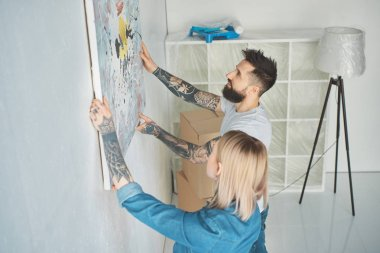 side view of young tattooed couple hanging painting on wall at new apartment