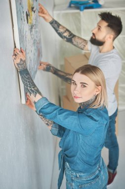 young tattooed couple hanging painting on wall at new apartment