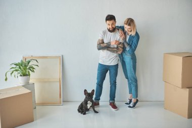 young couple standing at new home with cardboard boxes and french bulldog