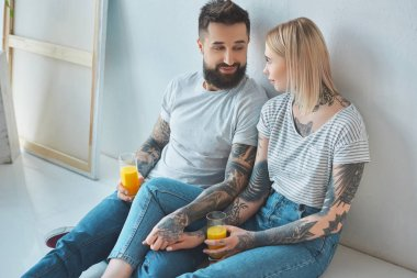 tattooed couple with glasses of juice holding hands while sitting on floor at new home