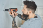 Fotografia tattooed man doing hole in wall with screw gun in new apartment, inexperienced millennial concept