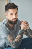 portrait of bearded man with tattoos looking at camera