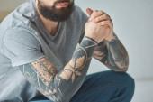 Fotografie Oříznout záběr vousatý muž s tetováním v šedé tričko