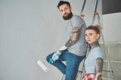 Fotografie Frau stehend auf Freund mit Roll Pinsel auf Leiter neue Zuhause