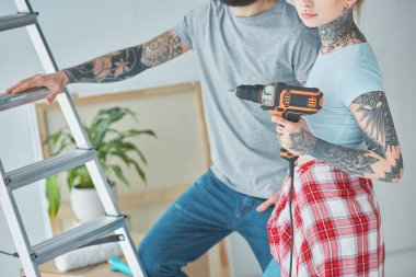 cropped shot of tattooed couple with screw gun standing at ladder at new home