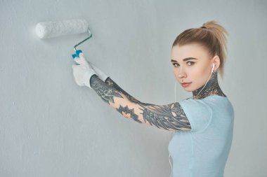 young tattooed woman in earphones painting wall at new home