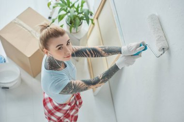 high angle view of young tattooed woman in earphones painting wall at new home