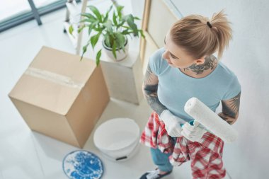 overhead view of tattooed woman with roll paint brush at new home