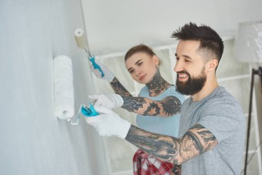 side view of young couple painting wall together at new apartment