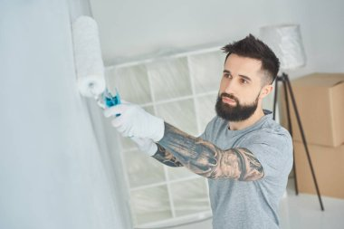 portrait of tattooed repairman painting wall in new apartment