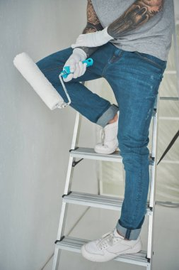 cropped shot of repairman with roll paint brush standing on ladder in new apartment