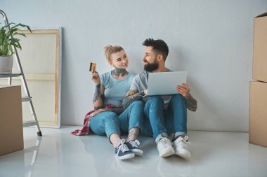 smiling couple with laptop and credit card shopping online at new home