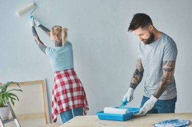 tattooed couple with roll paint brushes doing home repairment at new apartment