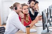Selektivní fokus úsměvu call centrum operátory pracující na pracovišti s kávou jít v úřadu