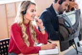 selective focus of smiling call center operator working in office
