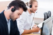 Photo selective focus of male call center operators in headsets at workplace in office