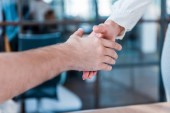Photo cropped shot of business partners shaking hands in office