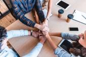 Schnappschuss von jungen Geschäftsleuten, die sich am Arbeitsplatz die Hände stapeln
