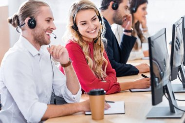 Selective focus of smiling call center operators working at workplace with coffee to go in office stock vector
