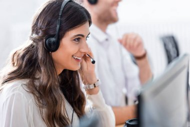 selective focus of smiling female call center operator in office
