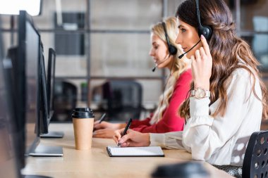 side view of female call center operators working at workplace in office