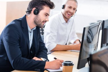 selective focus of male call center operators in headsets with notebooks at workplace in office