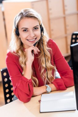 portrait of smiling female call center operator in headset at workplace in office