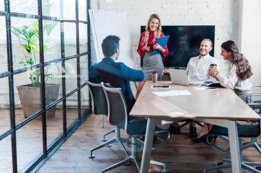 cheerful businesspeople having meeting in office