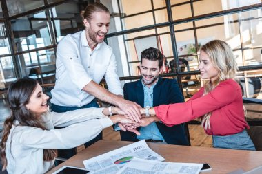 happy business team holding hands at workplace in office