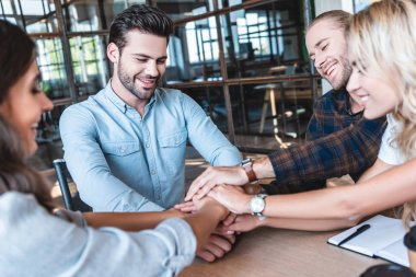 happy young business colleagues stacking hands at workplace
