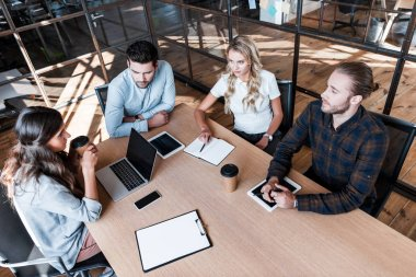 high angle view of young coworkers discussing project during business meeting