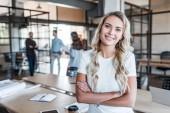 krásná mladá podnikatelka stojící s překřížením rukou a usmívá se na kameru v úřadu