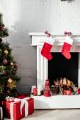 vánoční stromeček s cetky, dárkové krabičky a krb s vánoční punčochy doma