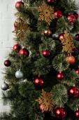 vánoční stromeček s cetky a zlaté vločky v pokoji