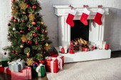 christmas tree with baubles, gift boxes and fireplace with christmas stockings in room
