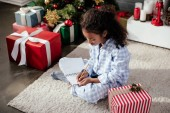 rozkošný africké americké dítě v pyžamu psát něco do copybook doma, vánoční koncepce