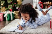 adorable african american child in pajamas lying on floor and writing something to copybook at home, christmas concept