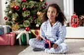 šťastné roztomilý africké americké dítě v pyžamu otevření vánoční dárek doma a hledat dál