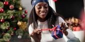 Fotografie usmívající se atraktivní africká americká žena doma otevření vánoční dárek