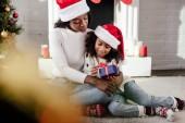 szelektív összpontosít, afro-amerikai anya santa kalap bemutató ajándék, hogy lánya otthon
