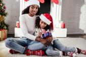 Fényképek afro-amerikai anya santa kalap átölelve lánya ajándék otthon