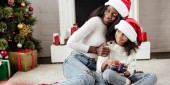 Fotografie smiling african american mother in santa hat presenting gift to daughter at home and looking away