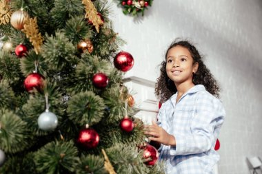 smiling adorable african american child in pajamas decorating christmas tree with baubles and looking away at home