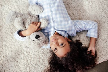 top view of adorable african american child in pajamas lying with teddy bear on carpet in room and looking at camera