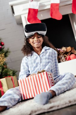 smiling adorable african american child in pajamas and virtual reality headset looking at christmas gift at home