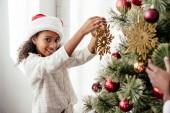 Teilansicht des afroamerikanischen Frau und Kind gemeinsam Weihnachtsbaum zu verzieren, die zu Hause