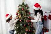 Fotografie africká americká matka a dcera v santa claus klobouky dekorační stromečky společně doma